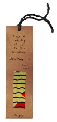 """Kitenge Fair Trade  African Proverb Rain River Bookmark  Kenya - Use this bookmark to hold your place in your favorite book or give as a gift to your teacher. Bookmark made of recycled paper and up-cycled kitenge fabric swatches. Fabric colors and patterns vary. Liberian proverb reads: """"A little rain each day will fill the rivers to overflowing"""" A fair trade product from Kenya. This bookmark was made by men of different ethnic groups who are working together to build strong homes, families…"""