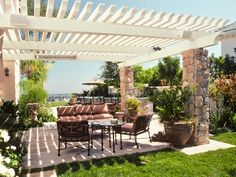 LOVE how Pergolas add instant charm and architectural interest to any patio. This shaded sitting area features comfy cushion chairs and shrubbery for a pleasant outdoor experience.