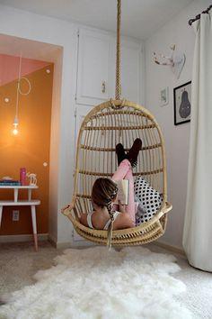 Hängekorbsessel und Fellteppich im Mädchenzimmer