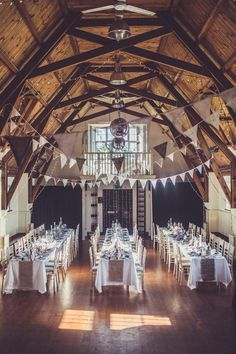 Village Hall wedding Venue decorated to perfection - Image by Claire Penn Photography - Suzanne Neville Lace Wedding Dress & Kurt Geiger Shoes for a Rustic Village Hall Venue decorated with gorgeous Bright Flowers, DIY Decor & Light Up Letters.