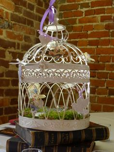 simple bird cage idea: decorated with  ceramic decoupage decorations elevated on a stack of interesting books with just tea lights and moss inside