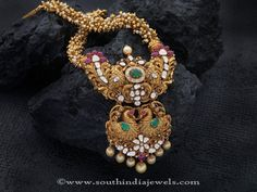 22k gold antique long haram with peacock pendant. The haram base is made of clustered peals and golden balls. The pendant is studded with sparkling white st