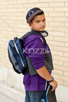 portrait of a fashionable teenage boy holding skateboard. - Side view portrait of a fashionable teenage boy holding skateboard, Model: Braden Beaudion