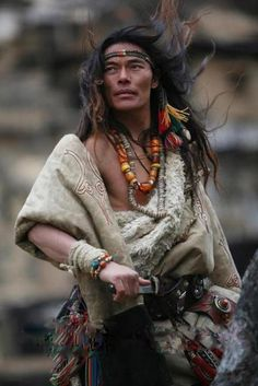 Tibetan man in traditional clothing and jewelry. It is traditional for Tibetan men to wear extravagant jewelry