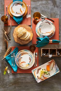 Influenced by the decorative plumes atop Pier 1's Feather Dinnerware, a creative color combination of blue and orange emerges in this feather tablescape. Natural elements take center stage with feathered quail figures, banded rope accents on handblown glassware and teak cutting boards that cleverly double as chargers. Come shop the trend.