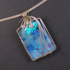 """Monet's Garden Fantasy in Blue No. 2 Dichroic Glass and Sterling Silver Wire Wrapped Pendant   Gorgeous dichroic glass wire wrapped pendant in sterling silver. The cabochon has blues, white, greens, and red and pink """"flowers"""". It reminds me of Monet's waterlily pond paintings. The chain is for display only and not included.  Pendant measures 2 inches long by 1 1/16 inches wide.  One of a kind.  Price: $45"""