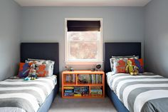 Graphic lines and clean symmetry characterize this contemporary kids' bedroom. Gray walls, bedding and carpet get a punch from orange accents, including a bookshelf that doubles as a nightstand and provides storage for books and games.