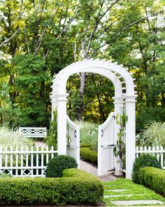 A graceful gated archway offers entrée into this formal perennial garden. The lush backyard was the vision of landscape architect Alec Michaelides, principal of Land Plus Associates.