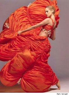 """Nylon parachute dress in International Orange, 1974. Kamali began experimenting with unusual materials, producing dresses and jumpsuits from parachute silks. To capitalize on the original use of the fabric these pieces were constructed with drawstrings in place in order to adjust the fit of the garment. Her 1975""""parachute"""" collection was a huge success. In later years, the material used would be changed to a more durable and water-repellent nylon."""