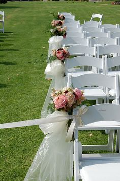 Flower bouquets and organza sheer ties off this wedding aisle