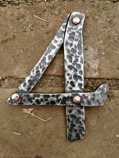 "Hand forged 6"" house number out of 1/4"" steel with copper rivets. Surface is hammer textured with a clear finish."