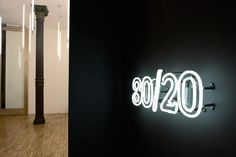 Open office loft, wood floors, white walls, cast iron columns, 13 ft high celings, white neon letters on gray wall, Magdalena Keck