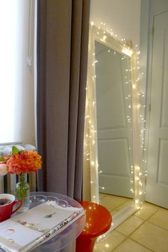Love this! Over-sized mirror draped with mini lights.