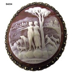c. 1930's pot metal and marcasite surround on this brown and white hand-carved scenic shell cameo pin/pendant of two women on the water's edge with goats and a dog and a European village across the sea. width