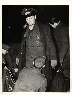 1941- Wearing his Iron Cross decoration, a German aviator is searched by a guard as he arrived with other German prisoners at an east Canadian port, enroute to internment camps.