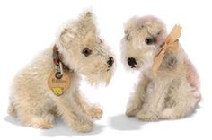 TWO STEIFF SMALL HEAD-TURNING DOGS, a seated Rattler, (3308,H), grey mohair, longer mohair beard and brows, brown, black and white glass eyes, black stitching, collar with two FF button and card tag, 1930s; and a seated Strupp, (3308,H), white and pink mohair, brown and black glass eyes, black stitching and FF button, 1930s --3½in. (9cm.) high (some wear and thinning)