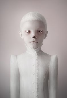 """Oleg Dou is a Russian photographer-artist that started manipulating photos at a young age. At 13 he was a pro in all things Photoshop and started off transforming images of friends and family. He now takes photos of children and then evolves them into otherworldly creatures. The first thing he does is erase their eyebrows and smooth their skin to erase their individuality. The series below is titled, """"Cubs""""."""
