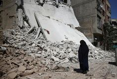 A woman walks past a damaged building after an airstrike in the rebel held Douma neighbourhood of Damascus, Syria September 9, 2016. REUTERS/Bassam Khabieh