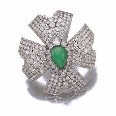EMERALD AND DIAMOND BROOCH, DAVID WEBB, 1970S Designed as a stylised Maltese cross, the cabochon pear-shaped emerald set within a border of pear-shaped diamonds, to the single- and brilliant-cut stone surrounds, mounted in platinum, signed David Webb.