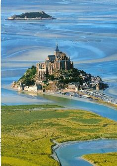 Mont St-Michel is a small rocky island about 1 km from the north coast of France at the mouth of the Couesnon River in Normandy. The mount is best known for the medieval Benedictine Abbey & steepled church that occupies most of the clump of rocks jutting out of the waters of the English Channel. Mont-Saint-Michel is connected to the mainland via a thin natural land bridge, which before modernization was covered at high tide & revealed at low tide, giving the mount a mystical quality.