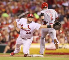 St. Louis Cardinals first baseman Matt Adams is drawn off the bag by an errant throw from pitcher Michael Wacha as Cincinnati Reds' Zack Cozart reaches safely and advances to second on the error in seventh inning action during a game between the St. Louis Cardinals and the Cincinnati Reds on Friday, April 17, 2015, at Busch Stadium in St. Louis.