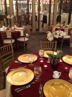 Burgundy linens, gold chargers, gold chivari chairs with ivory pads, simple orchid centerpieces, votive candles