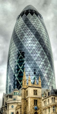30 St Mary Axe, AKA the 'Gherkin'. St. Andrew Undershaft is the church in front; The Gherkin could well be the ugliest tower I've ever seen -- definitely a carbuncle on London's face!!