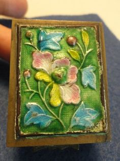 A cute brass with enamel stamp box. 1 5/8 X 1 1/4 X 1 1/8 deep. A wonderful special trinket box. Impressed with China on underside. I found many of these boxes when researching this item. I still love it. Very good colors. Floral design. Hinge is very good condition.