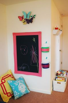 DIY: Reuse a large frame and a piece of sheet metal to make a chalkboard. Mount it low on the wall for easy kid access. Also hang some painted galvanized buckets filled with calk. Toss in some floor pillows.