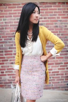 Pink tweed skirt + mustard cardigan + white silk blouse. I personally wouldn't wear so many layers of pearls. I would wear a nice watch to toughen it up a little for office/business.