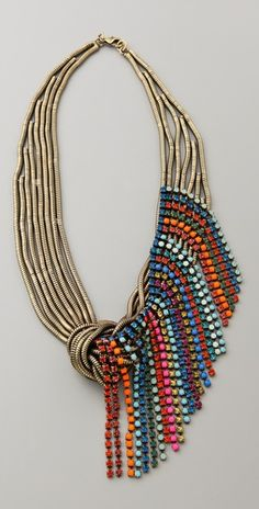 This antiqued brass snake-chain necklace features Swarovski crystal fringe at the knot detail. Lobster-claw clasp.