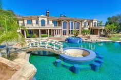 The backyard resembles a luxury resort, with an enormous infinity edge pool that features a grotto, a foot bridge to a swim-up/sit-down bar, a huge spa, and a water slide. Swimming Pool Plan, Swimming Pool Waterfall, Amazing Swimming Pools, Luxury Swimming Pools, Luxury Pools, Cool Pools, Swimming Pool Architecture, Spa Interior, Infinity Edge Pool