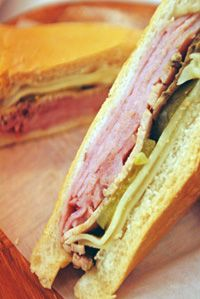 A REAL Cuban sandwich does not contain anything but the following: Cuban-style Roasted pork (sliced), serrano ham (I love Serrano ham), Swiss cheese, pickles on buttered Cuban bread, pressed and hot. I do add mustard because I really like it that way. But anything else, really is unnecessary.
