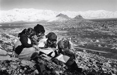 Kurdish School girls revising their math work while the remnants of a village destroyed by the iraqi army and tents of IDPs haunts the background. Southern Kurdistan, 1992.