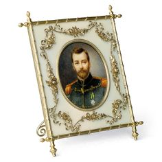 A FABERGÉ SILVER-GILT AND GUILLOCHÉ ENAMEL PHOTOGRAPH FRAME WITH A MINIATURE PORTRAIT OF TSAR NICHOLAS II ON IVORY, WORKMASTER MIKHAIL PERCHIN, ST PETERSBURG, CIRCA 1890. Upright rectangular form, the oval aperture with beaded bezel, enamelled in translucent oyster white over a sunburst engine-turned ground, applied with floral garlands, a crossed ribbon-tied reeded border, the corners set with six cone finials, ivory back with silver-gilt scroll strut.