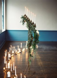 A tall wrought iron candelabra dripping with foliage held up long white candlesticks that illuminated the ceremony space. Several candlesticks and votive candles also spread around the wood floors inside the room.
