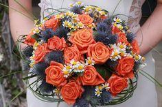 Oranžová varianta svatební kytice v krásném elegantním kulatém tvaru, slavnostní růži poprovází svou prostou krásou heřmánek a eryngium.