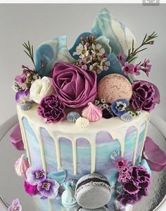 Purple, blue and white elegant drip cake complete with flowers, chocolate bark and macaroons.