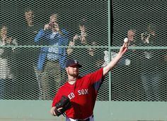 #WorldSeries2013 Fans take pictures from inside a viewing area in the Fenway Park outfield as Boston Red Sox pitcher Jon Lester throws during team baseball practice in Boston, Monday, Oct. 21, 2013. Lester is scheduled to be the starting pitcher in Game 1 of the World Series against the St. Louis Cardinals on Wednesday. (AP Photo/Elise Amendola)