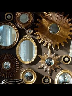 A collection of gold mirrors against a dark wall creates a mesmerizing effect that reflects throughout the room, opening up the space without using a full-length mirror.