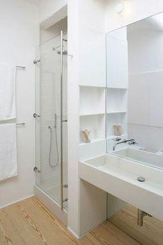 L'astuce gain de place : pour optimiser l'espace dans une petite salle de bains, il est astucieux d'aménager des niches de rangement dans le renfoncement crée par la cabine de douche.