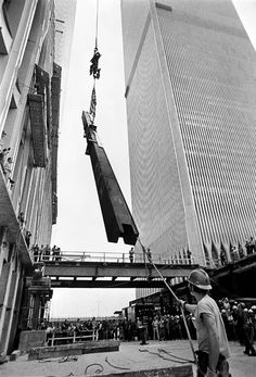 During the topping off ceremony, a worker helped to stabilize the last steel beam as it was hoisted to the top of the South Tower of the World Trade Center, July 19, 1971. The ceremony is held when the last beam is placed at the top of a building. Photo by Neal Boenzi/The New York Times