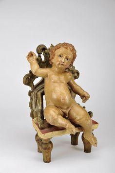 Designação: Menino Jesus sentado em cadeira; Material: escultura em madeira policromada; Descrição: olhos de vidro; Origem: portuguesa; Época: séc.