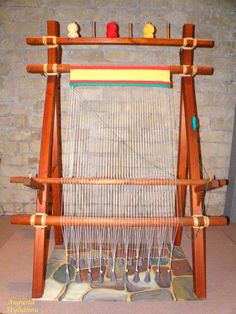 Example of a warp-weighted loom, a civilization-driving technology. The warp yarns hang freely from a bar supported by upright poles which can be placed at a convenient slant against a wall. Bundles of warp threads are tied to hanging weights called loom weights which keep the threads taut. Evidence of the warp-weighted loom appears in the Neolithic period in central Europe. It is depicted in Minoan frescoes
