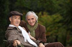Elegant elderly couple sitting on a park bench - stock photo