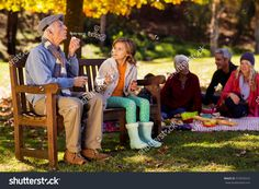 Grandfather blowing bubbles with granddaughter while family having breakfast at park during autumn