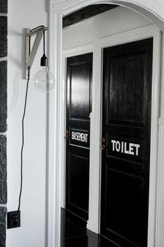 diy lampa, diy lampa med glödlampa i sladd som hänger på konsol på väggen, svartmålade dörrar, svarta dörrar med vit text, hall, svart och vitt, inspiration, inredning, inredningstips, svarta stora klinkersplattor, golv hall, valv mot hall och kök, svarta kontakter,
