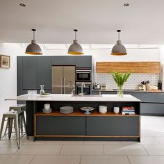 As in nature, earthy greys, browns and sand colours work together harmoniously. As this modern kitchen demonstrates, grey needn't look cold as lots of shades have warmth to them. Grey can work in darker kitchens, too. Just pair it with pale surfaces, such as the worktop, metro tiled splashback and flooring shown here, which draw the eye, add interest and reflect light.  Cabinetry: Roundhouse Paint: Down Pipe from Farrow & Ball  Painted kitchen design ideas | Decorating | housetohome.co.uk