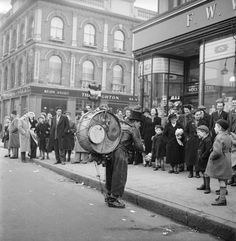 A one-man band performs to the crowds outside Woolworth's, Camden. 1952