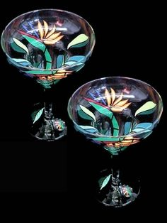 This set of (2) margarita glasses are colorfully hand painted with bird of paradise blossoms sporting magnificent plummage. Brilliant orange petals are contrasted with arrow shaped tongues of vivid blue. This exotic flower is named after paradise itself.